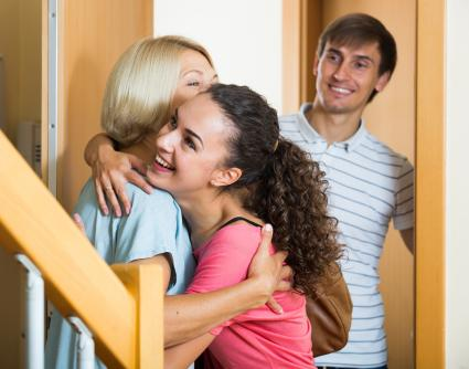 Happy mature mother meets son with his fiancee at doorway