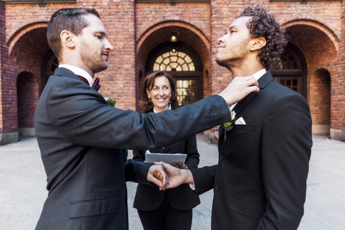 Man adjusting bow tie of male partner in front of priest during wedding ceremony