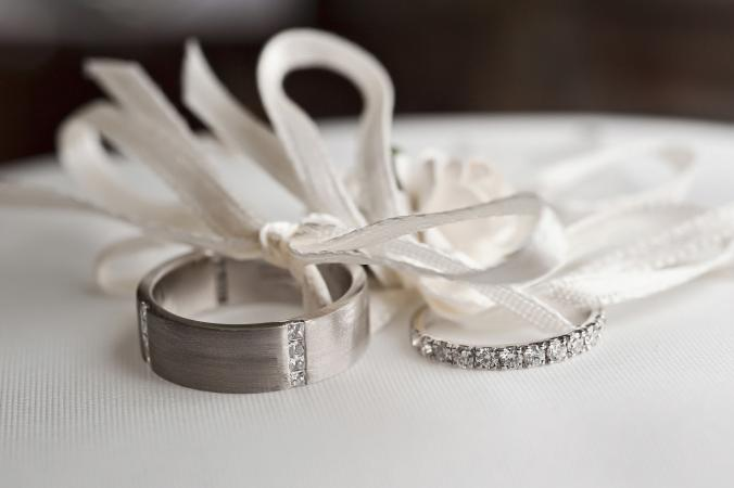 Wedding rings tied to pillow with white ribbon