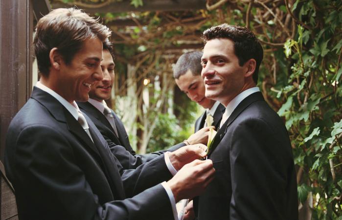 Groomsman adjusting groom's boutonniere