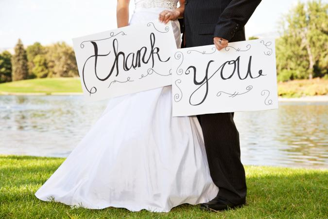 Young Wedding Couple Holding Thank You Signs