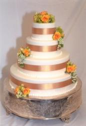 4-tier round wedding cake with flowers and ribbons