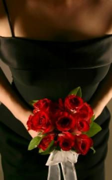 Bridesmaid in a black dress carrying red roses