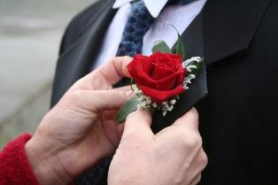 Mother of the groom pinning his boutonniere on