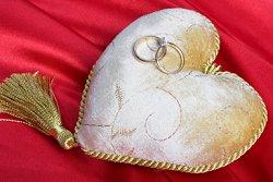 Wedding rings attached to a heart-shaped pillow