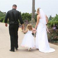 Bride and groom walking with the flower girl
