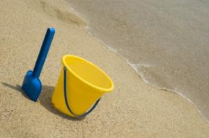 Yellow plastic beach pail and blue shovel