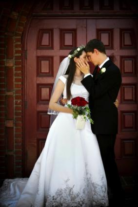Groom kissing his bride in front of the church