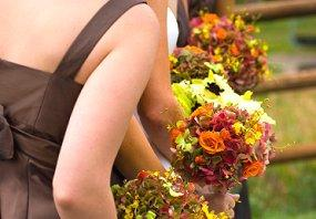 Bridesmaids in brown dresses and carrying autumn bouquets
