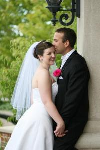 Groom kissing his bride outside on the porch