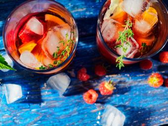 Glasses of sangria garnished with fruit and thyme
