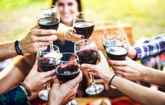 Hands toasting red wine
