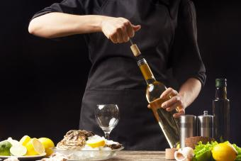 Chef opens Italian dry wine with oysters with lemon