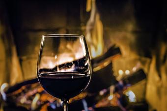 A glass of red wine standing in front of the fireplace