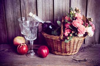 wicker basket and a bottle of rose wine with two wineglasses and nectarines