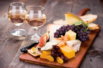 Cheeseboard filled with an assortment of cheeses and served with dessert wine