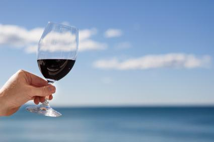 Hand holding glass of red wine.