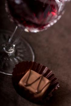 Glass of red wine with chocolate candy