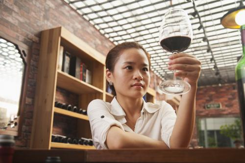 Woman looking at a glass of red wine