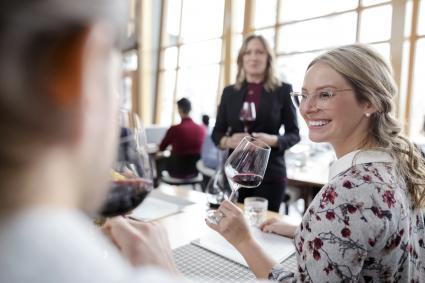 Smiling woman tasting red wine