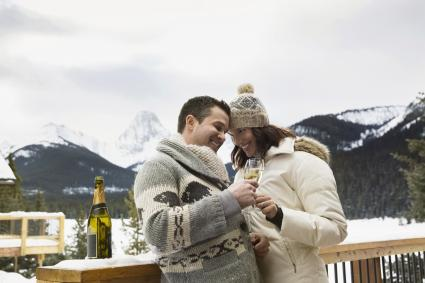 Couple enjoying champagne on snowy deck below mountains