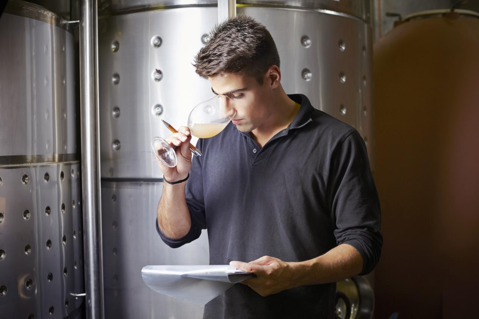 Wine expert smelling white wine sample