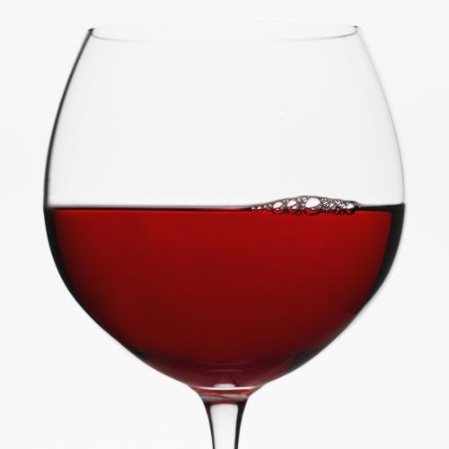 Red wine balloon glass on white background