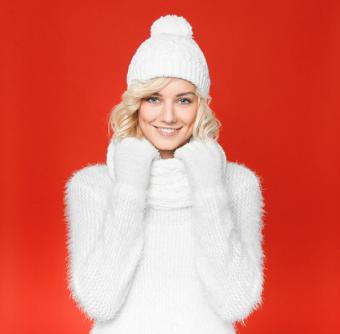 Woman wearing white knit cap and sweater