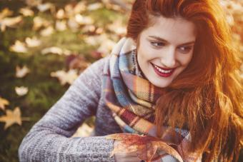 Woman in a gray fall sweater and scarf