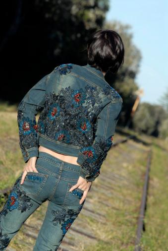 Woman wearing embroidered designer jacket and jeans
