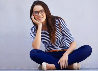 Classically styled smiling woman sitting on floor