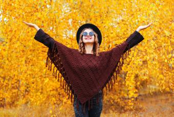 Woman wearing knitted burgundy poncho