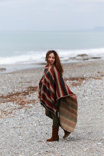 On beach with full-length poncho