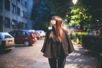 Girl wearing black poncho at night