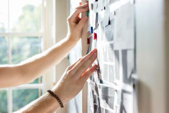 Person pinning mood board ideas to wall