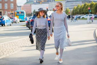 Amelie Stanescu and Tina Haase wearing dresses with leggings outside Baum und Pferdgarten on August 11, 2021 in Copenhagen, Denmark - Getty Editorial Use