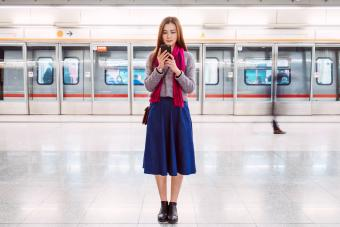 Young woman wearing a midi skirt waiting for train