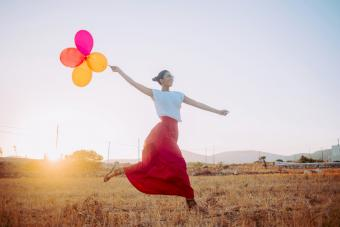 Young woman wearing a red maxi skirt running threw the field holding balloons