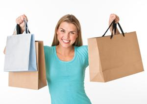 Petite woman holding up shopping bags