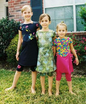 Three young sisters in modest swimsuits