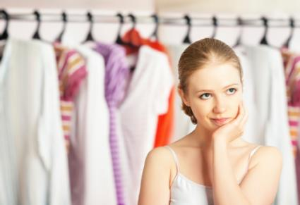 Woman chooses clothes in the wardrobe closet