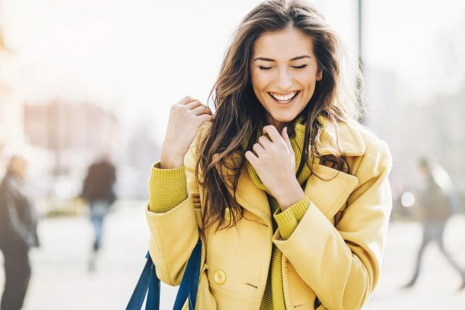 Happy woman wearing a yellow fall coat