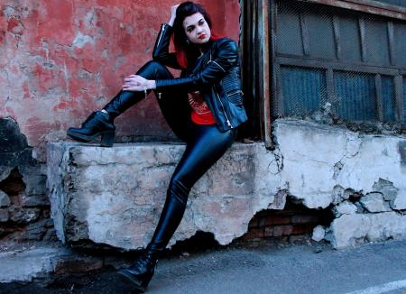 Rocker style woman posing in alley