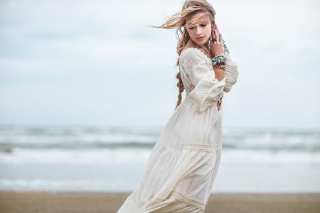 Boho girl in white dress on beach