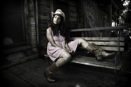 Cowgirl in dress sitting on porch