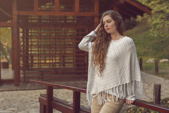 Woman wearing knit poncho outdoors