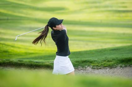 Woman hitting ball out of bunker
