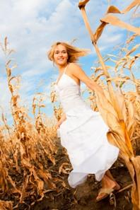 Image of a woman in a white peasant dress in a cornfield
