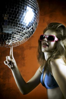 Woman in a disco outfit touching a mirror ball