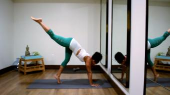 Woman lifting first leg up to handstand